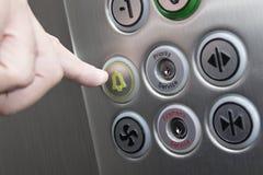 Zeigefinger, der den Warnungsknopf im Aufzug drückt lizenzfreie stockfotografie