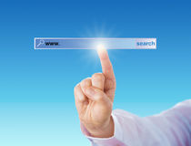 Zeigefinger, der ein leeres Suchmaschine-Werkzeug berührt Stockfotografie