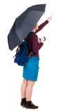 Zeigefrau mit einem Rucksack unter einem Regenschirm Stockfotos