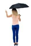 Zeigefrau unter einem Regenschirm Lizenzfreies Stockfoto