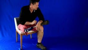 Zeigen auf: Gut aussehender Mann kommt, er sitzt auf dem Stuhl und den Spielen, um mit seiner Prothese, Punkte zu fliegen drei Pl stock video footage