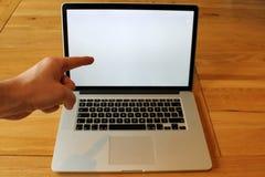 Zeigen auf leeren Laptop mit der linken Hand stockbild