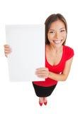 Zeigen der Frau, die weißes leeres Zeichenplakat hält Stockbilder