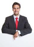 Zeigen des hispanischen Geschäftsmannes mit Klage und des weißen Brettes Lizenzfreie Stockfotografie