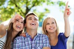 Zeigen mit drei junges Freunden Lizenzfreie Stockbilder