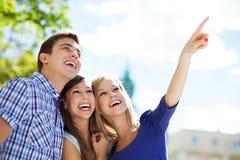 Zeigen mit drei junges Freunden Stockfotos