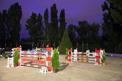Zeigen Sie springende Hürden auf der Rennbahn am Abend Stockfoto