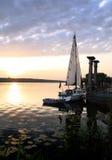 Zeilboot bij meer op de zonsondergang Stock Afbeeldingen