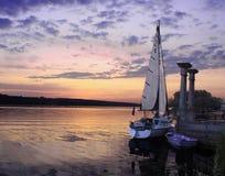 Zeilboot bij meer op de zonsondergang Royalty-vrije Stock Afbeelding