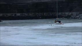 Zeilboot die door een grote golf bij de ingang van een haven ten val wordt gebracht stock videobeelden