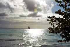 Zeilboot die op de oceaan in de zonsondergang varen stock afbeelding