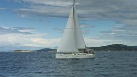 Zeilboot die op het overzees drijven Kustlijn op achtergrond stock video