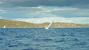 Zeilboot die op het overzees drijven Kustlijn op achtergrond stock videobeelden