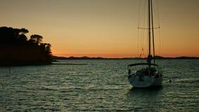 Zeilboot die op het overzees tijdens zonsondergang drijven Kustlijn op achtergrond stock footage