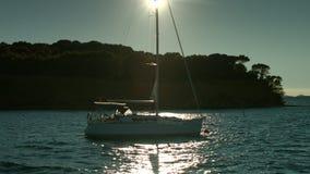 Zeilboot die op het overzees tijdens zonsondergang drijven Kustlijn op achtergrond stock videobeelden
