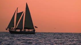 Zeilboot die op kleurrijke zonsondergangachtergrond varen