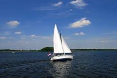 Zeilboot, die over een rivier vaart stock afbeeldingen