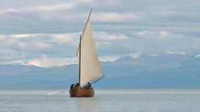 Zeilboot door wazige bergen stock footage