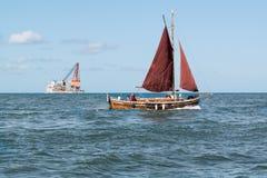 Zeilboot en groot schip op zee dichtbij Rotterdam, Nederland Royalty-vrije Stock Afbeeldingen