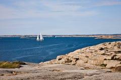 Zeilboot en rotsachtige kust royalty-vrije stock foto's