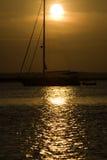 Zeilboot in het plaatsen van gouden zon Stock Afbeeldingen