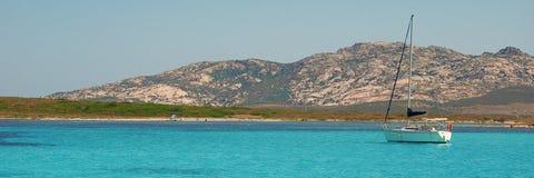 Zeilboot in mediterraan strand sardinige Blauw water royalty-vrije stock afbeelding