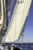Zeilboot met opstellingszeilen die in open zee bij zonsondergang glijden stock afbeeldingen