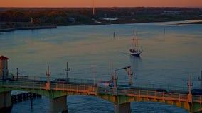 Zeilboot met passagiers die door een brug in een rivier bij zonsondergang varen stock footage