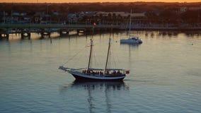 Zeilboot met passagiers die door stadsbaai op een rivier bij mooie zonsondergang varen stock video