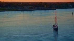 Zeilboot met passagiers die door stadsbaai op een rivier bij zonsondergang varen stock videobeelden