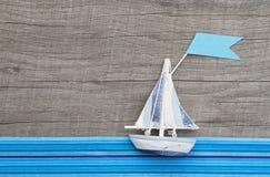 Zeilboot met vlag op grijze houten achtergrond met blauwe strepen Stock Fotografie