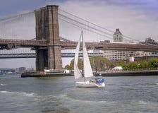 Zeilboot op de hudsonrivier die op de brug New York sluiten van Manhattan stock foto