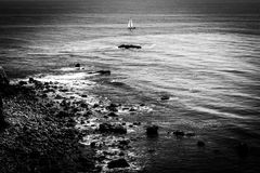Zeilboot op oceaan met dramatische rotsachtige kustlijn Stock Fotografie