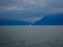 Zeilboot op water met bergen Stock Fotografie
