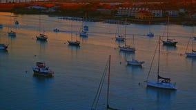Zeilboten bij een rivier door een stadsbaai bij warme zonsondergang worden verankerd die stock video