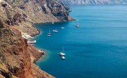 Zeilboten en jachten dichtbij vulkanische rotsen van Santorini-eiland, Griekenland Stock Afbeelding