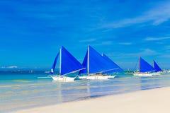 Zeilboten met blauwe zeilen op een tropisch strand Reis en de zomer royalty-vrije stock foto