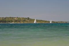 Zeilboten op blauwe overzees met kust achter hen Royalty-vrije Stock Afbeeldingen
