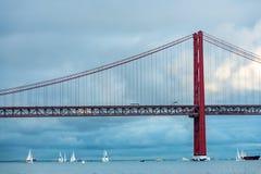 Zeilboten rond de brug van 25 DE Abril in Lissabon Stock Fotografie