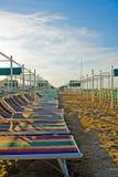 Zeile von deckchairs auf Sandstrand Stockfotografie