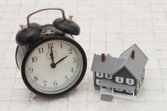 Zeit, ein Haus, graues Haus A und Wecker auf Stein-backg zu kaufen Lizenzfreie Stockfotos