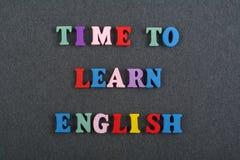 ZEIT, ENGLISCHES Wort auf dem schwarzen Bretthintergrund verfasst von den hölzernen Buchstaben des bunten ABC-Alphabetblockes, Ko stockfotografie