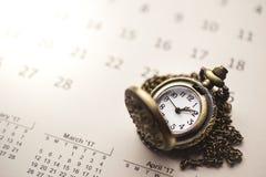 Zeit für die Aufwartung mit Weinlese-Taschen-Uhr auf dem Kalender und dem s Stockbilder