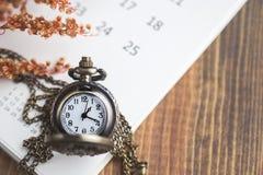 Zeit für die Aufwartung mit Weinlese-Taschen-Uhr auf dem Kalender und dem W Lizenzfreies Stockfoto