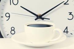Zeit für eine Kaffeepause, Arbeit mit Kaffeetasse und Uhr bei zehn O-Uhr auf Weiß Stockbilder
