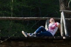 Zeit für entspannen sich, Dame, die auf Holzbrücke sitzt Stockfotografie