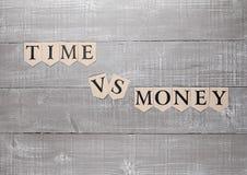 Zeit gegen Geldpapier-Buchstabesymbol-Motivationszeichen Lizenzfreie Stockfotos