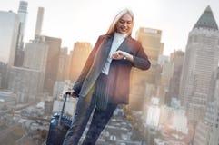 Zeit, Geschäft zu tätigen Nette Geschäftsfrau in der klassischen Abnutzung die Zeit und lächelnde die Weilestellung gegen überprü stockfotos