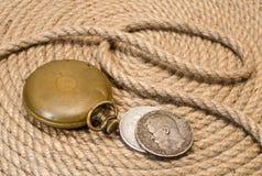 'Zeit ist Geld' - alte Taschenuhr- und Silbermünzen auf Hanf rope Hintergrund Stockbilder