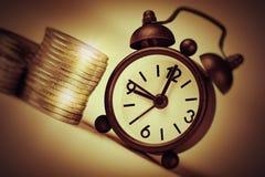 Zeit ist Geld Konzept alte Uhr und Stapel Euromünzen Lizenzfreie Stockbilder